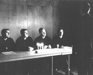 Student standing before four member court