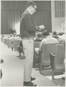 A student recording the names of absent students during chapel, 1967.
