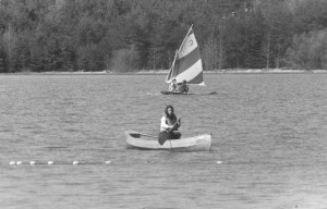 Two people on a sail boat and another person in a canoe on the lake