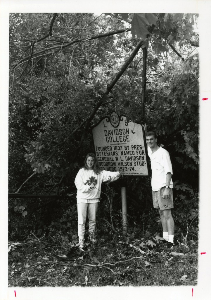 Students with the Davidson College historical marker on campus, behind them are multiple broken branches hanging and on the ground, illustrating the amount of debris on September 22, 1989.