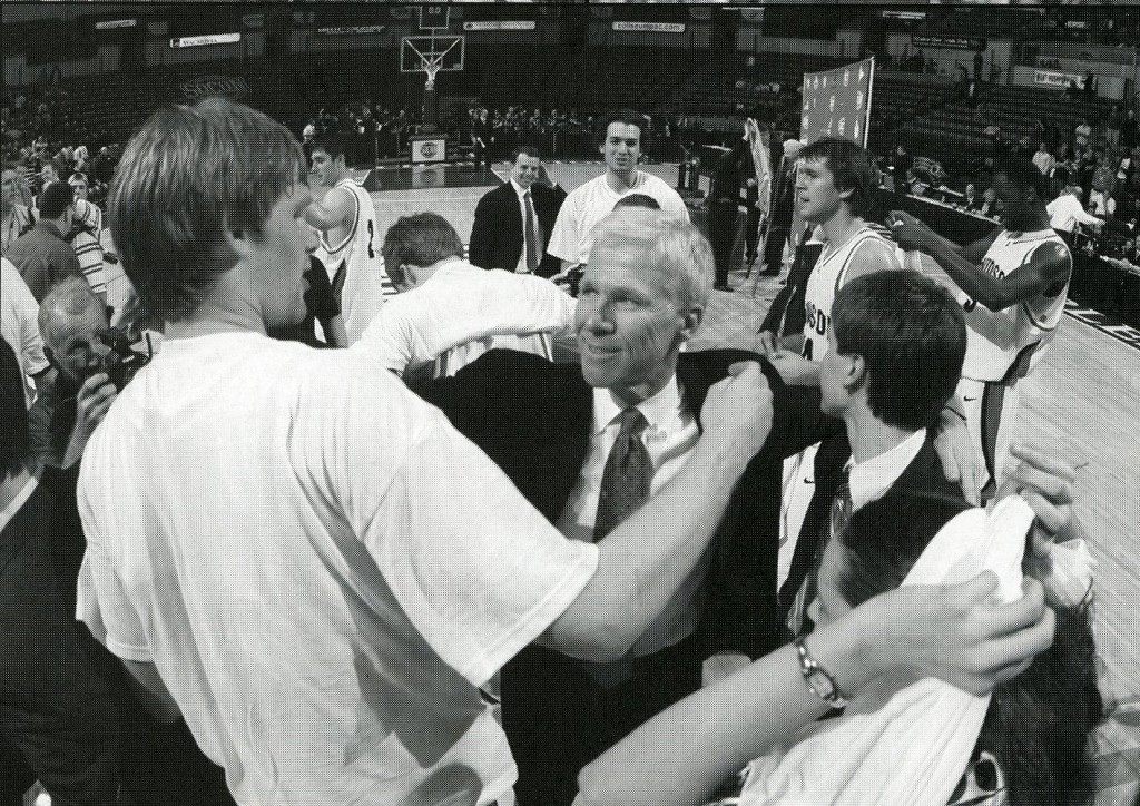 McKillop on the court with players, from the 2009 - 2010 media guide.