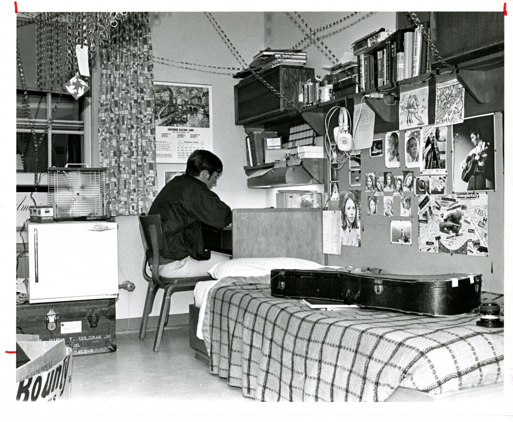John Cronin's (Class of 1971) dorm room in 1969 provides a glimpse into his hobbies and loved ones - the guitar case, headphones, and photo of a musician speak to his interest in music. Whether the chains serve a functional or aesthetic purpose is unclear, however (photograph taken by George Sproul, Class of 1970).