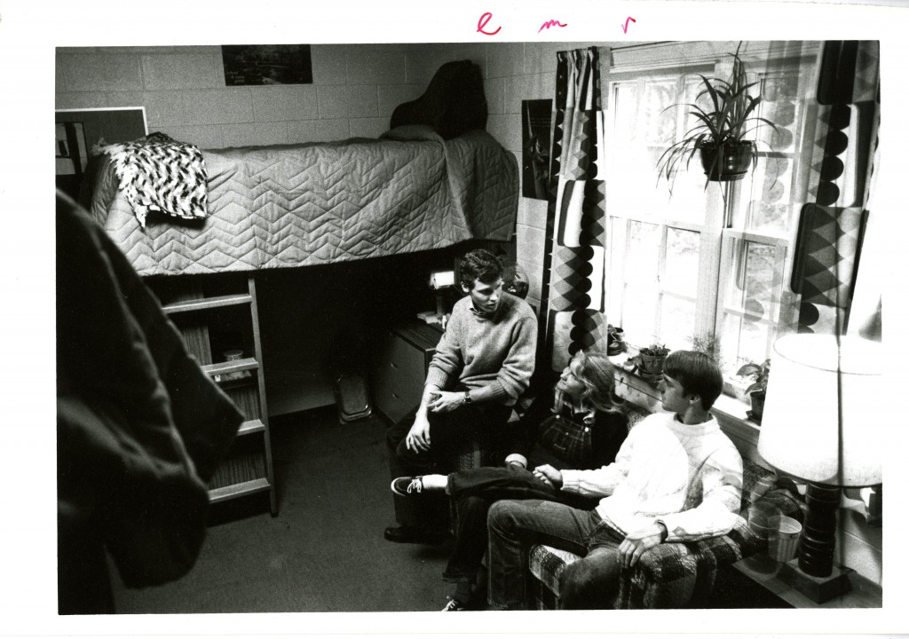 Three students gather in a mid-1980s dorm room - note the lofted bed, now a very popular dorm room modification.