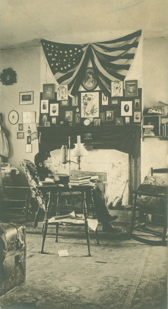 Kemp Elliott Savage (Class of 1906) sits in front of a very elaborately decorated dorm room gallery wall (including a draped flag), circa 1902.