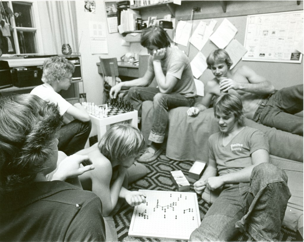 A group of students play games in a Richardson dorm room in 1975 - a peek at the walls in the background reveals some typical dorm decorations, including a wall calendar.