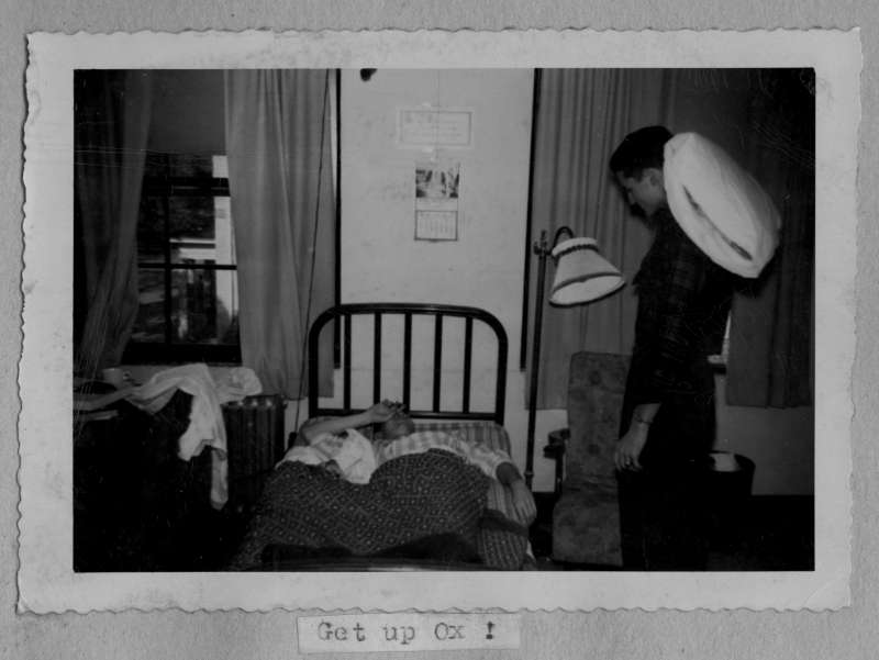"""Get up Ox!"" - a sleepy student is awakened in Georgia dorm, under his decorations. This photograph is from a 1948 Phi Gamma Delta scrapbook."