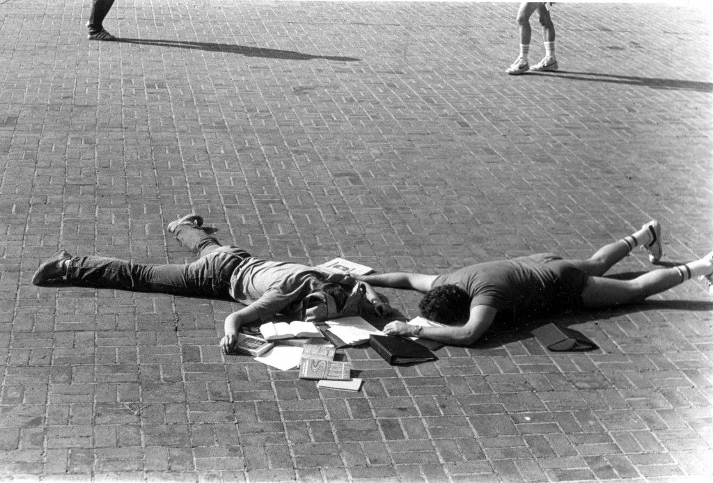 Two students make the most of studying outdoors, circa 1994.