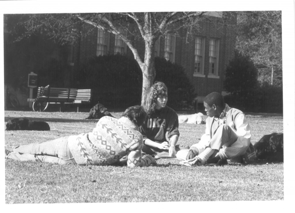 Reggit Leggett, Andrea Ward, and John Hain sit on the lawn in the grass studying and talking. There are three black dogs and one white one lounging around as well.