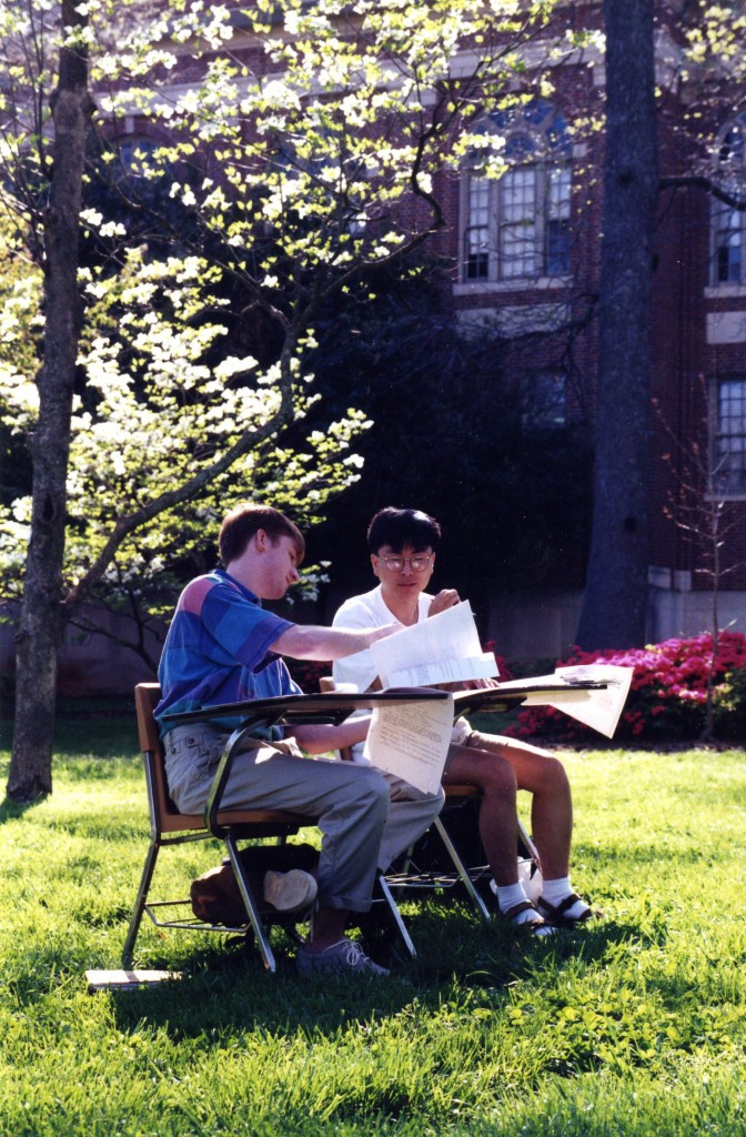 Jin Hyuk Chang  and Theodore Edward Curey (both Class of 1996) study at desks outside, 1996.