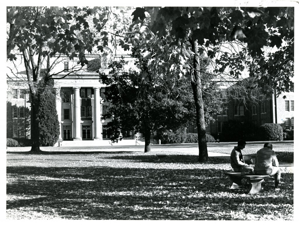 Two unknown students study on a bench with Chambers Building in the background.
