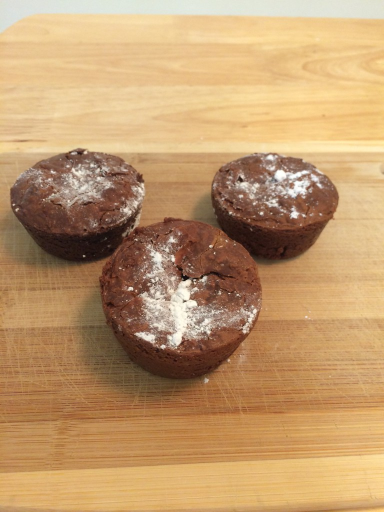 Three round luscious brownies topped with powdered sugar.