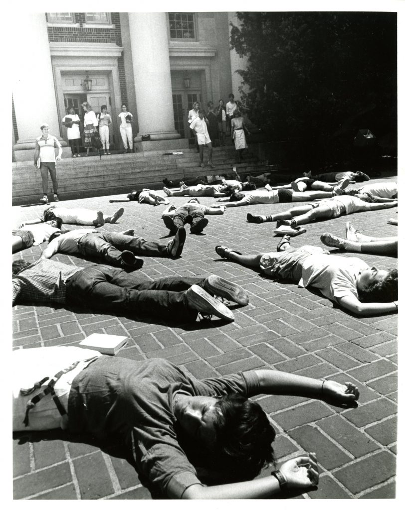 A photo capturing students participating in the die-in inf front of Chambers Building.