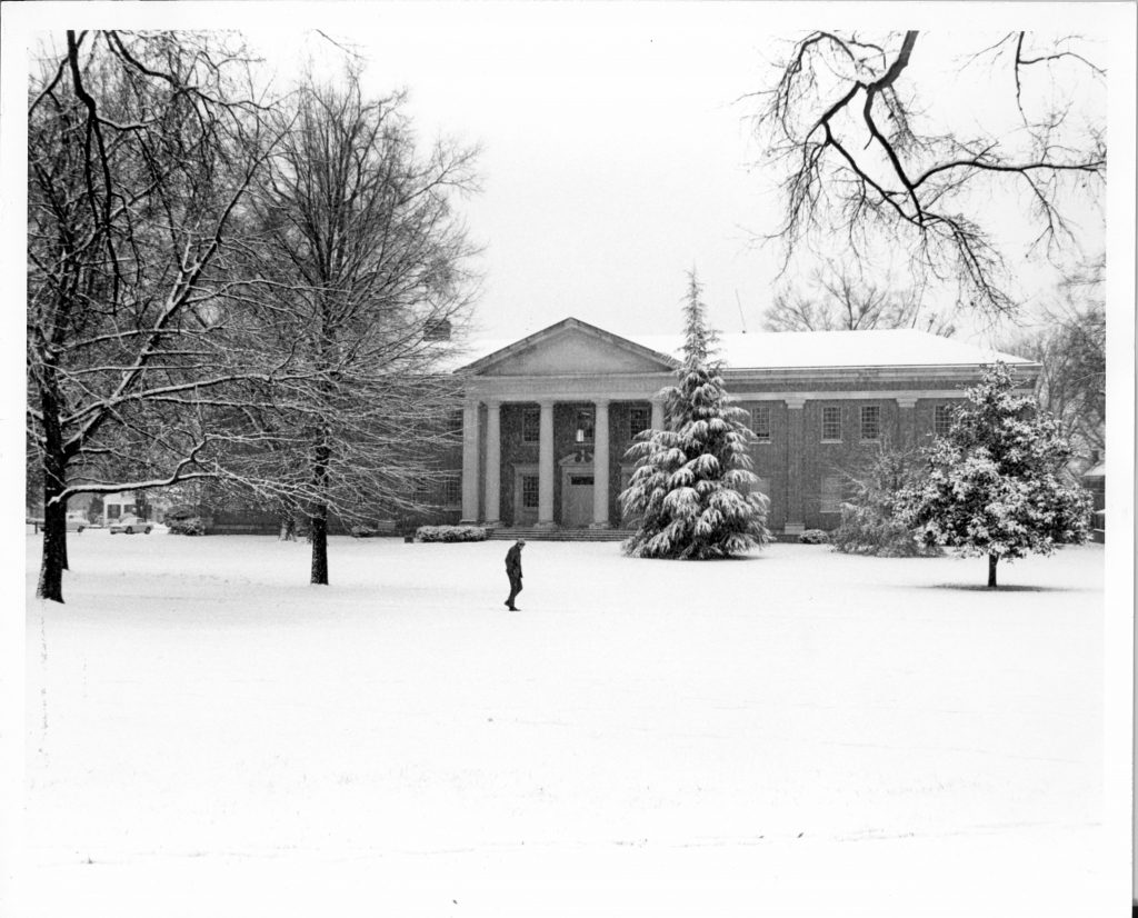 A lone figure walks past Dana Science Building in the snow, 1969.