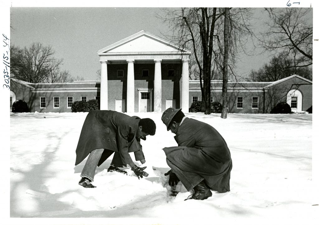 Two students play in the snow in front of Cunningham, circa 1975.