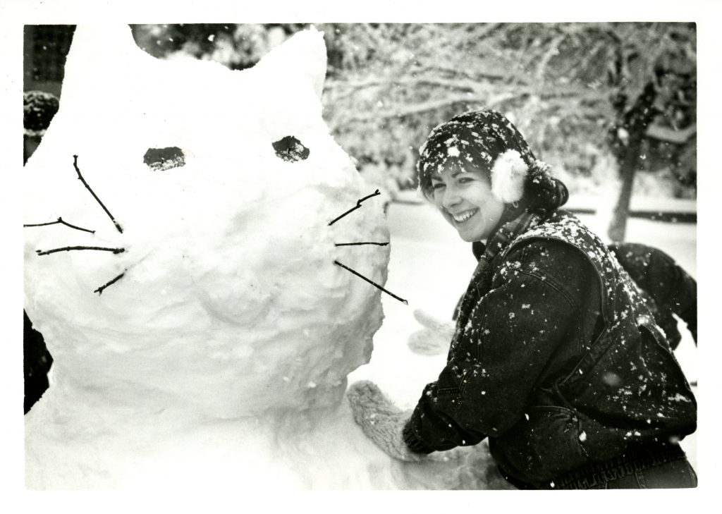 A student looking over her left shoulder toward the camera leaning on a large snow cat she just made.