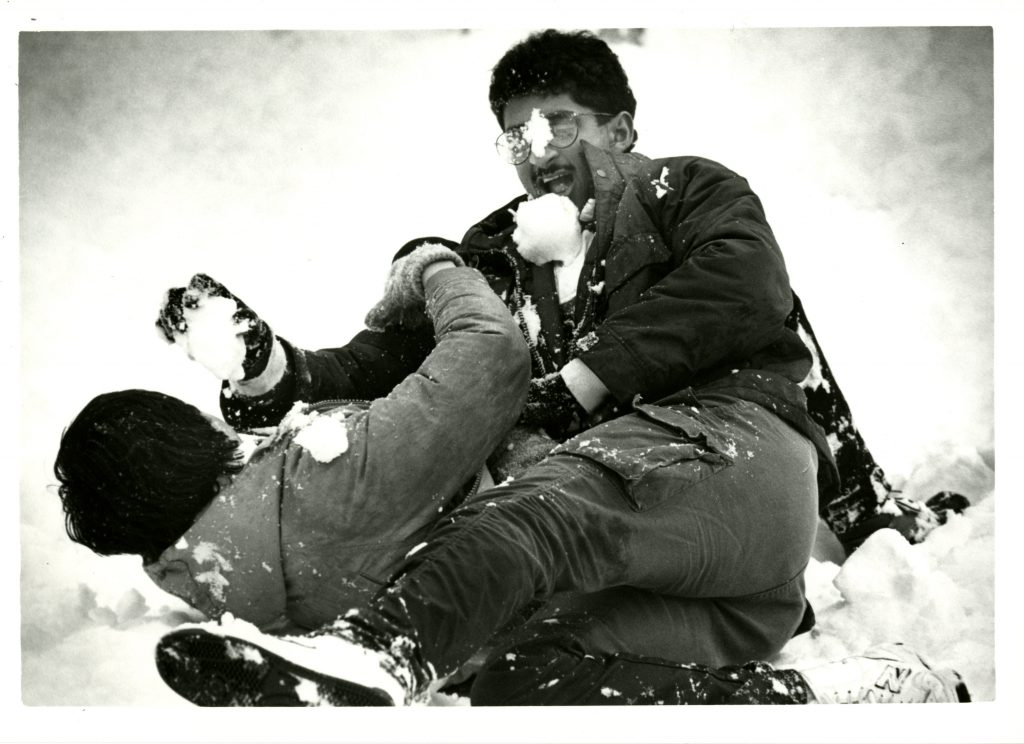 Two students engage in a rowdy snow fight on the ground, 1987.