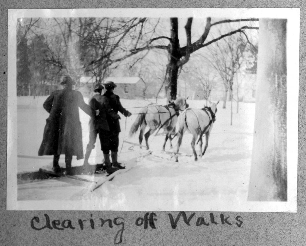 "Three students clear walkways on rails pulled by horses captioned, ""Clearing off Walks"", circa 1915."