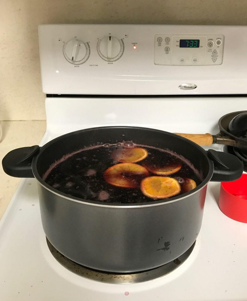 Glogg heating on my stove, complete with orange slices.