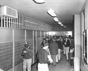 Area with students PO boxes in the 1960s, many students gathered in front of the samll square boxes in the walls
