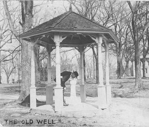 A man drinking from the drinking fountain in the old well circa 1924