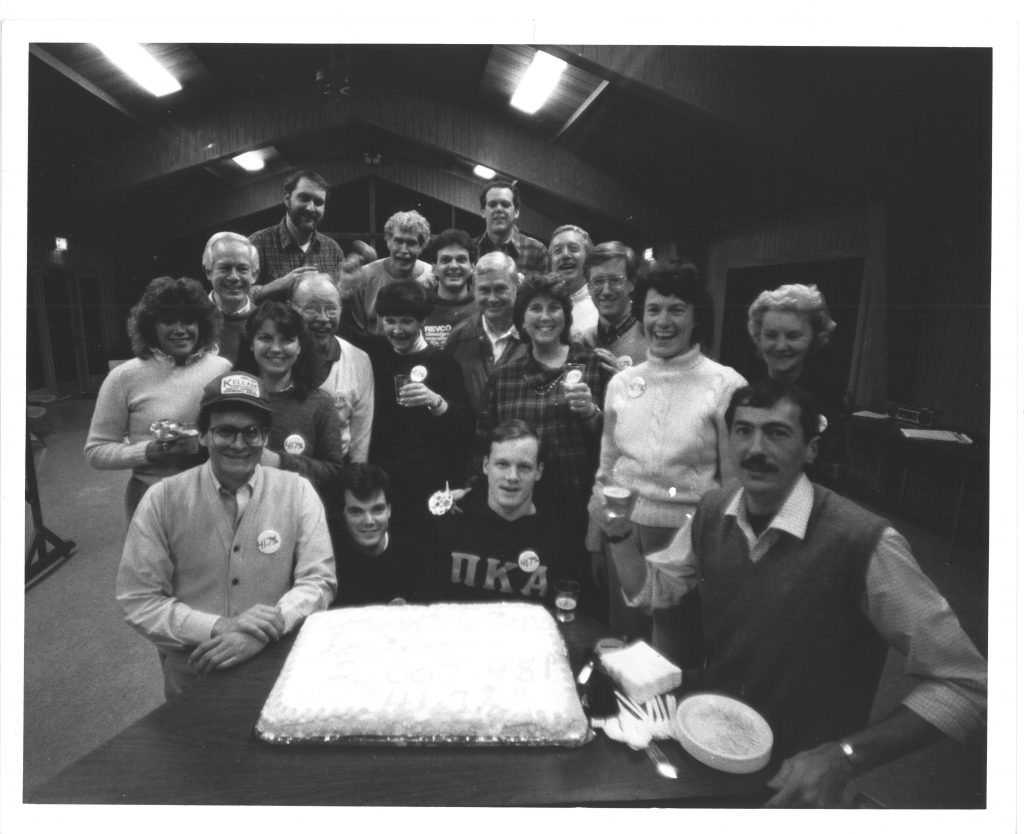 "Davidson employees gather around a cake with icing spelling out ""Congratulations Davidson, 2,007,481, 41.7%"" at a Development retreat in 1986. Bill is seated far right, next to the cake."