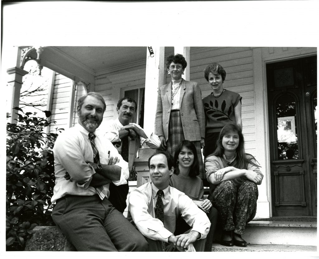 College Communications staff in front of the Copeland House in 1990. From left to right: Jerry Stockdale, Bill Giduz, Pat Burgess, Barbara Mayer, Amy Burkesmith, Michele Miller, and Mike Van Hecke.