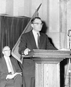Sam Spencer as Dean of Students standing at a podium with President John Cunningham in the background.