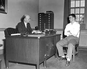 "Bailey in 1949 with a student. It is not clear if any of this books on his desk is a ""Doom Book of Absences."""