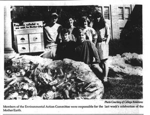 1990 Earth Day trash display, students standing next to large plastic bags filled with trash, one of them holding a sign