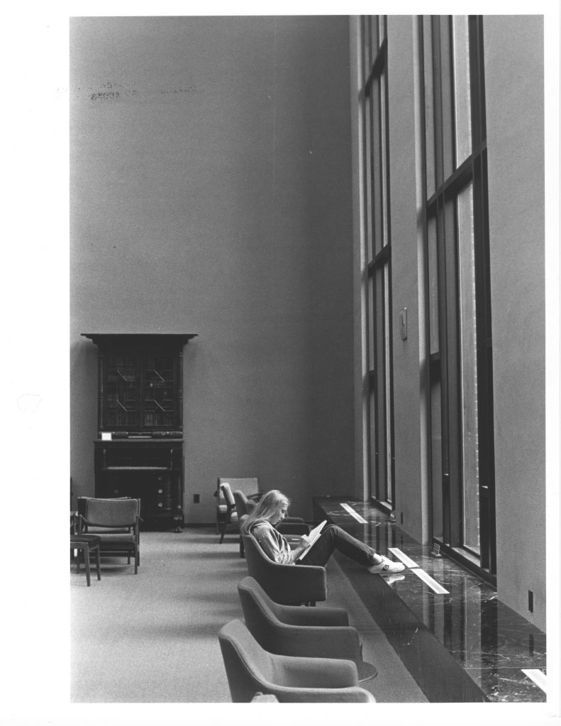 A student reads in front of the large windows in Little Library, circa early 1970s.