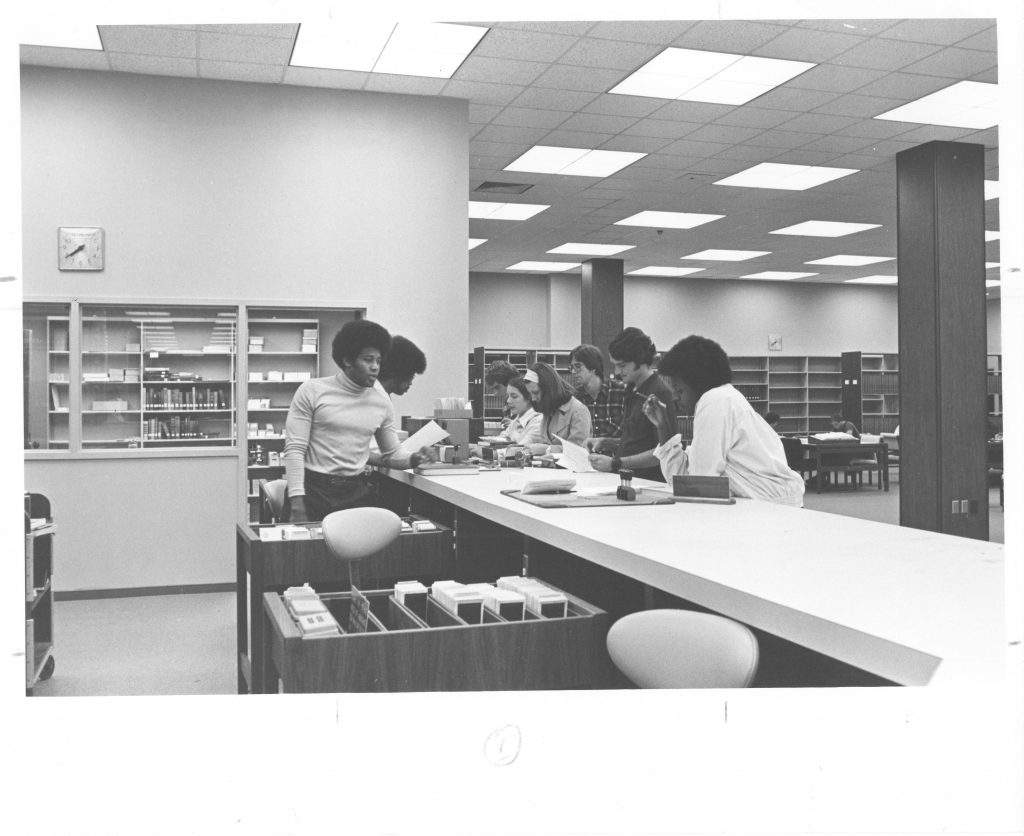 A group of students gather at the circulation desk in Little Library, September 18, 1974.