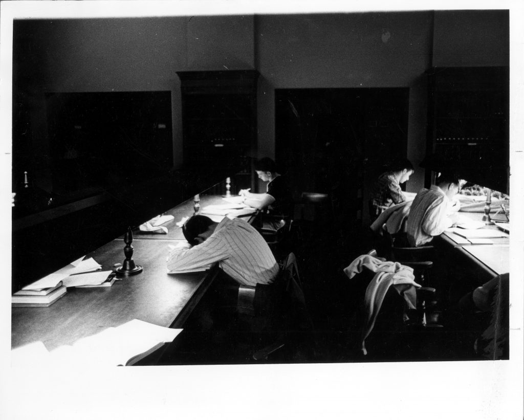 A student sleeping in the Grey Library reading room while two others study, circa 1960.