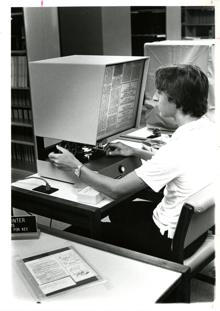 A student uses the microfilm reader in Little Library, circa 1980s.