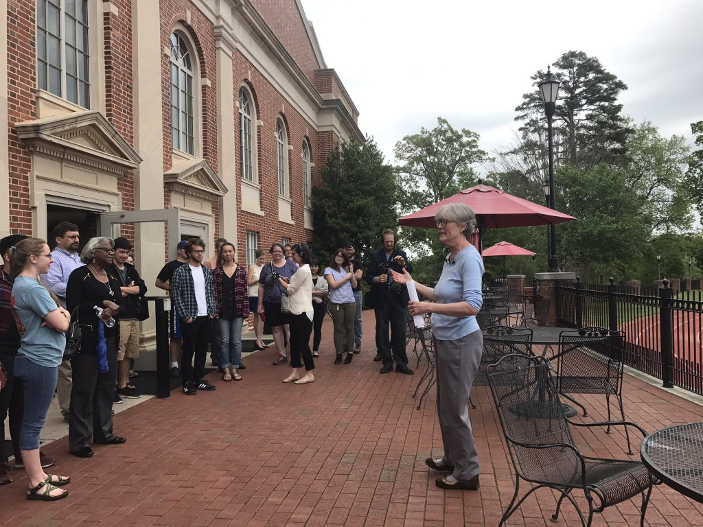 Jan addresses the crowd at her final campus history tour outside of the union on the patio facing the football field in April 2017