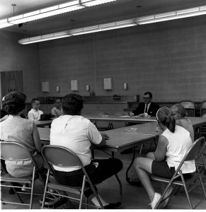 Alumni Weekend, June, 1963, Dr. William Hight, Director of Student Counseling sitting at the head of four tables formed into a sqaure talking to parents and their children