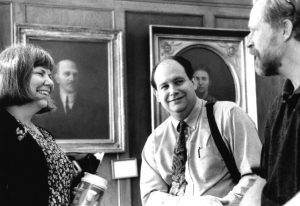 Past AAG Officers, Marcia Makl, Kurt C. Holmes, William Brown standing before a portrait gallery ca. 1996-2001