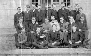 Three rows of young men in suits stand in front of windows.