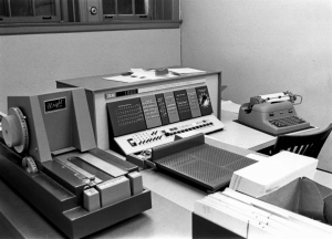 An IBM 1620 Computer from the early 1960s sits atop a table. A locked shelf is in the background