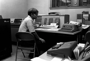 A bespectacled boy of about 14 sits in a folding chair in front of the IBM 1620 computer circa 1963.
