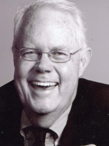 Headshot of a laughing man wearing glasses, black and white.