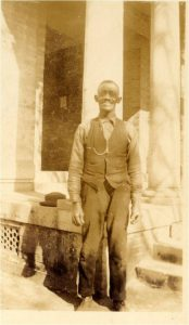A sepia-toned photograph of a black man in a vest and dress slacks standing in front of a columned building