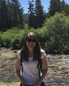 Woman on a mountain trail wearing a white t-shirt and black sunglasses.