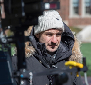 A man in a parka and winter hat stands behind film cameras.