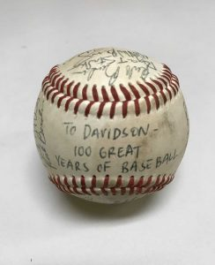 "A baseball with ""To Davidson - 100 Great Years of Baseball"" and signatures of past players on it."