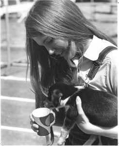 Student with puppy drinking from a cup