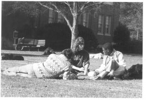 Three students in 1984 study with dog pals.