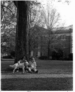 Two students in front of Chambers pet a white dog.