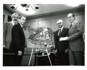 Four men surround new aerial image of the college campus.