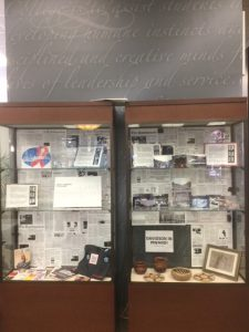 Glass exhibit cases filled with artifacts and articles about AIDS at Davidson