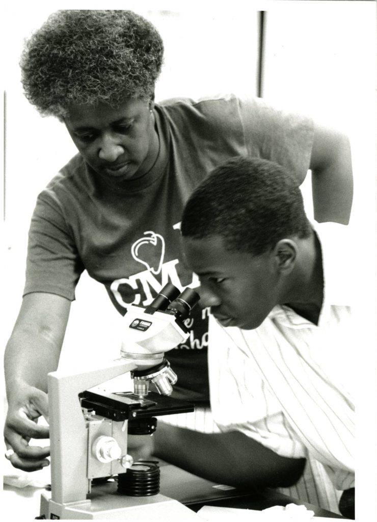 A black professor assists a black student with a microscope as part of the 1995 Love of Learning summer program.